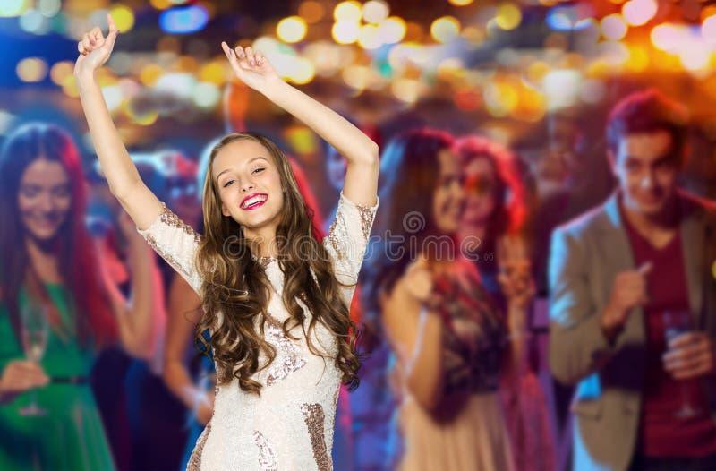 Jovem mulher feliz ou dança adolescente no clube do disco imagem de stock
