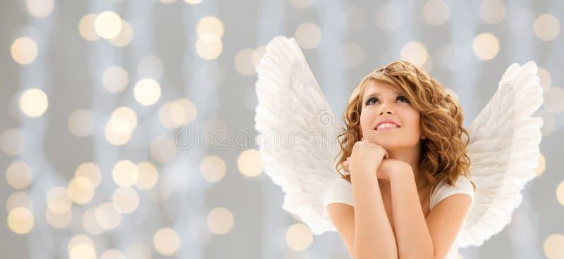 A jovem mulher feliz ou a menina adolescente com anjo voam fotos de stock