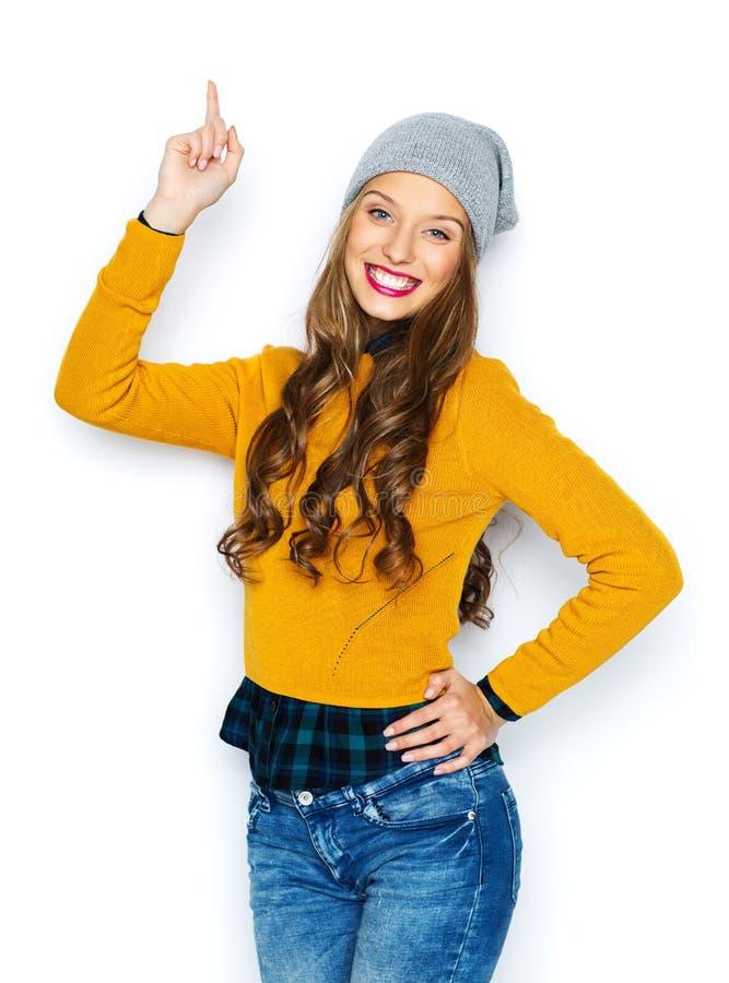 Jovem mulher feliz ou menina adolescente que apontam o dedo acima imagem de stock