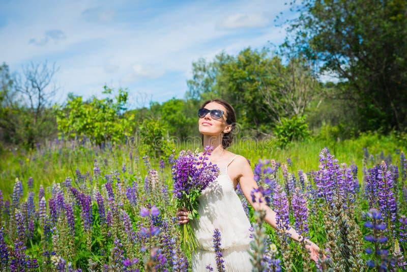 Jovem mulher, feliz, posição entre o campo dos lupines violetas, sorrindo, flores roxas Céu azul no fundo verão, com imagem de stock