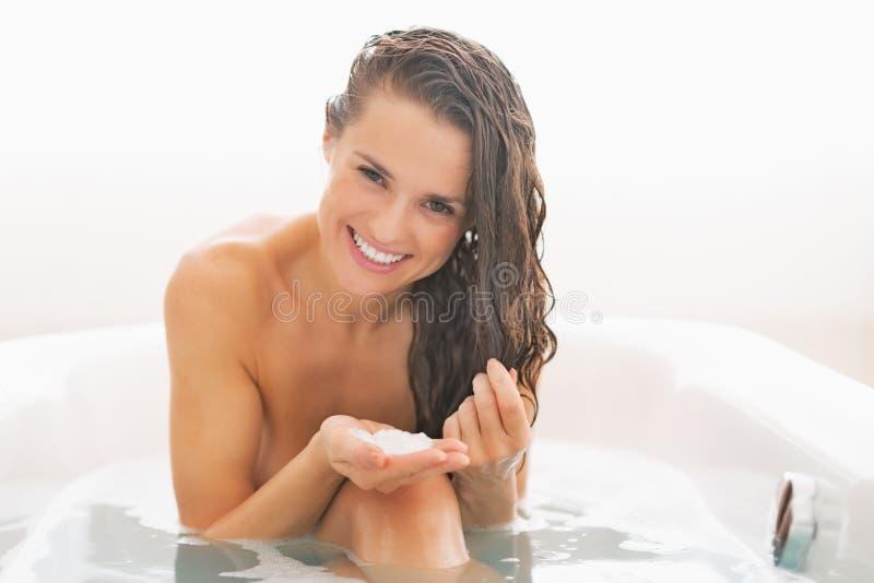 Jovem mulher feliz que aplica a máscara do cabelo na banheira fotografia de stock