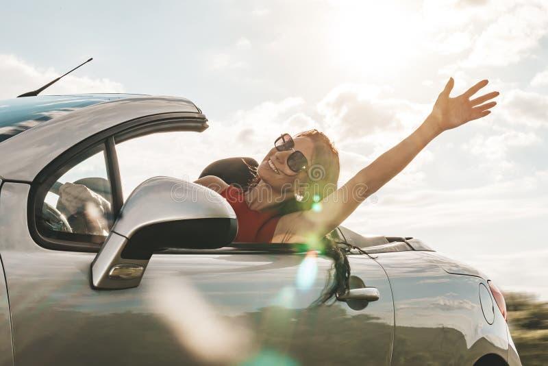 Jovem mulher feliz que aprecia um passeio em um carro convert?vel Cumprimento da m?o conceito do curso e da aventura da estrada m fotos de stock royalty free