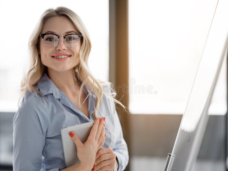 Jovem mulher feliz que apresenta seu projeto novo do negócio fotografia de stock