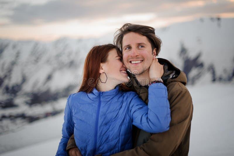 Jovem mulher feliz que beija seu noivo de sorriso nas montanhas fotos de stock royalty free