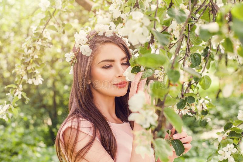 A jovem mulher feliz que cheira flores na mola da flor floresce imagem de stock