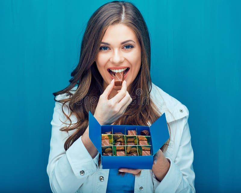 Jovem mulher feliz que come doces de chocolate fotografia de stock