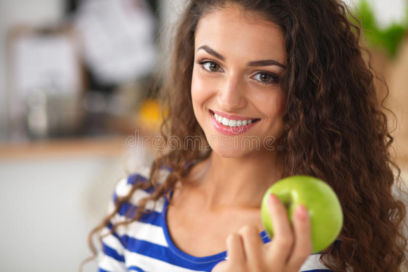 Jovem mulher feliz que come maçãs na cozinha imagem de stock