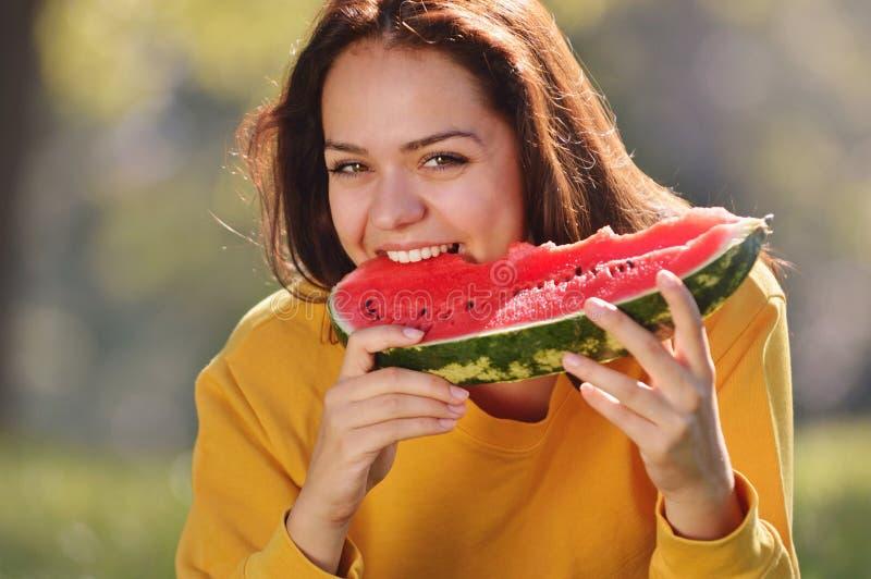 Jovem mulher feliz que come a melancia no parque imagens de stock