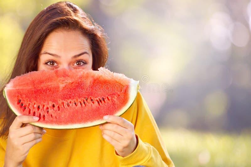 Jovem mulher feliz que come a melancia no parque imagem de stock
