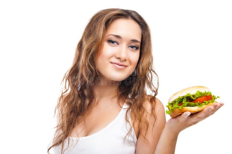 Jovem mulher feliz que come o hamburguer saboroso grande isolado fotos de stock