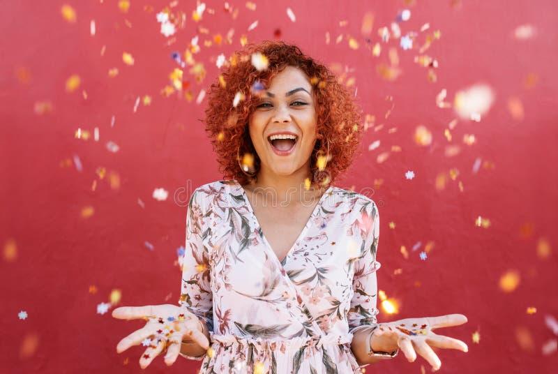 Jovem mulher feliz que comemora com confetes toda ao redor imagens de stock royalty free