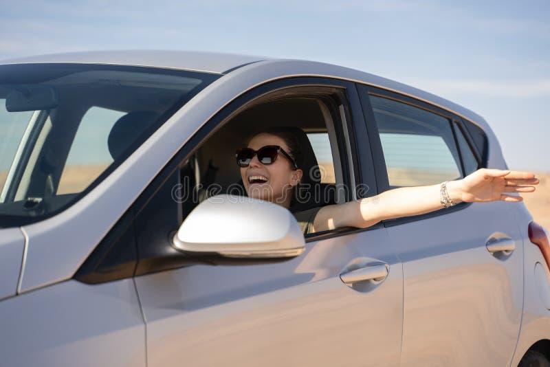 Jovem mulher feliz que conduz um carro alugado no deserto de Israel imagens de stock