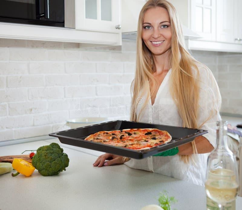 Jovem mulher feliz que cozinha a pizza em casa fotografia de stock