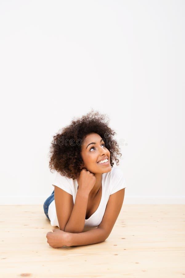 Jovem mulher feliz que encontra-se na fantasia do assoalho imagens de stock