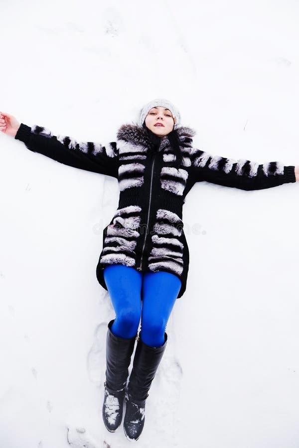Jovem mulher feliz que encontra-se na pele da neve no inverno imagens de stock royalty free