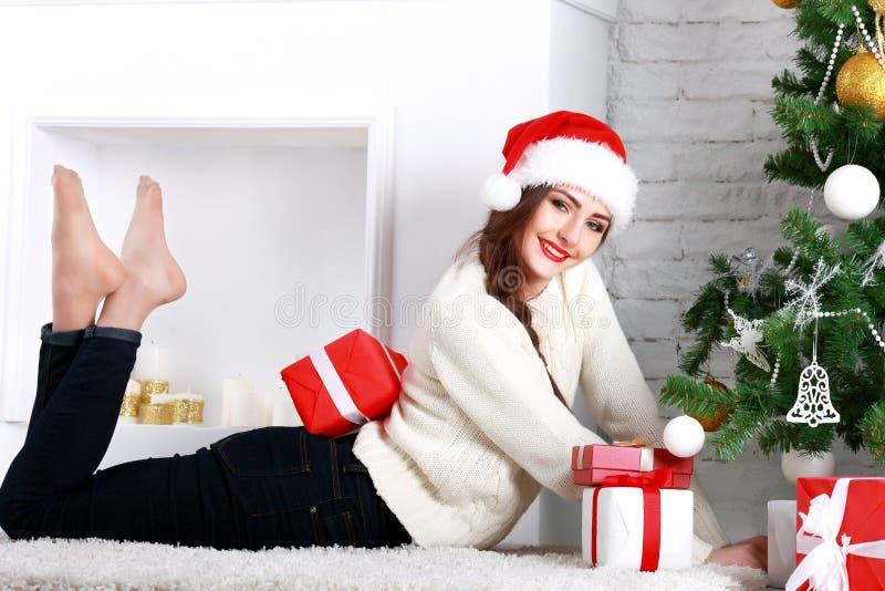 Jovem mulher feliz que encontra-se no assoalho com caixa de presente imagens de stock royalty free