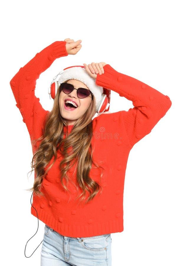 Jovem mulher feliz que escuta a música do Natal foto de stock royalty free