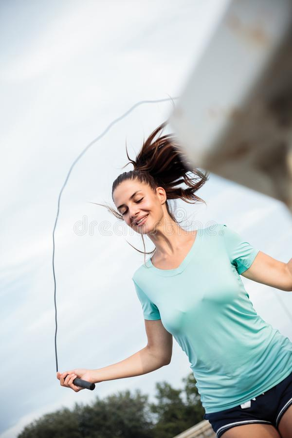Jovem mulher feliz que exercita, corda de salto em uma ponte fotos de stock
