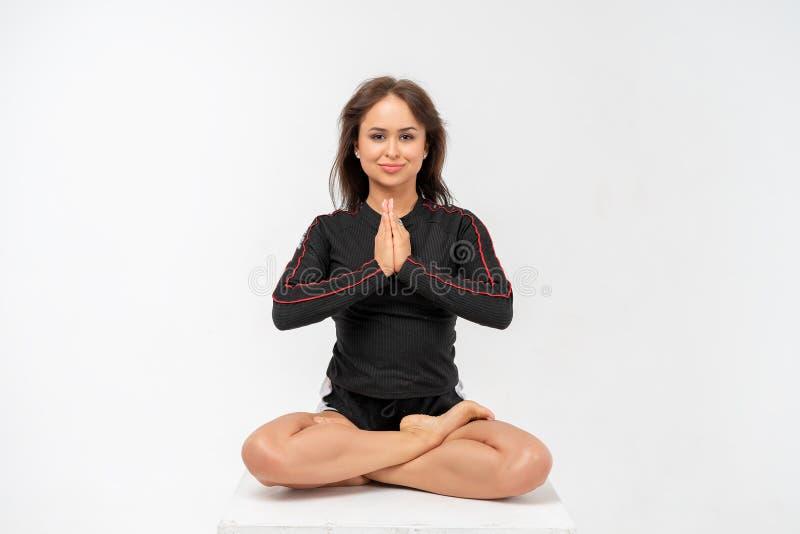 Jovem mulher feliz que faz a ioga no fundo branco imagem de stock