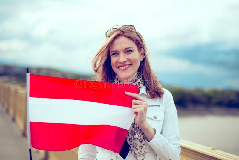 Jovem mulher feliz que guarda a bandeira austríaca na ponte fotos de stock royalty free