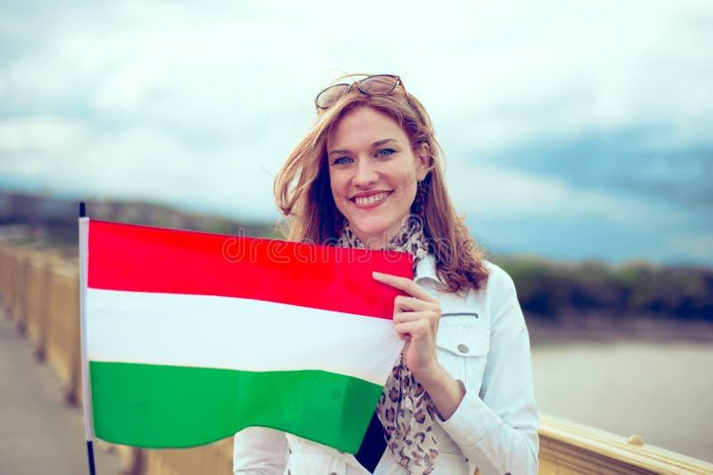 Jovem mulher feliz que guarda a bandeira húngara na ponte imagens de stock royalty free