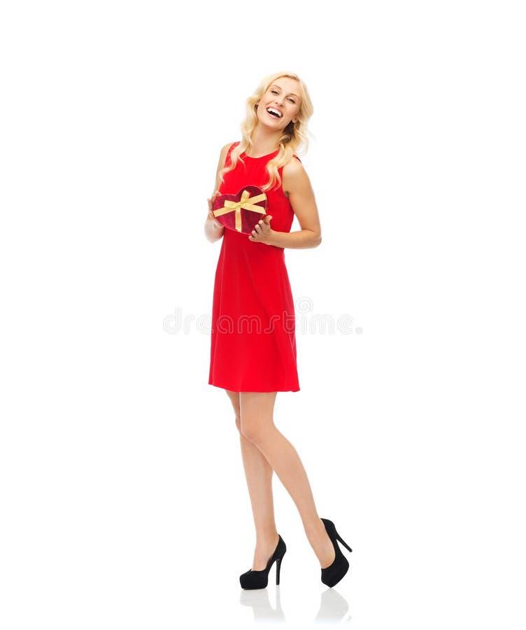 Jovem mulher feliz que guarda a caixa de presente dada forma coração fotos de stock royalty free