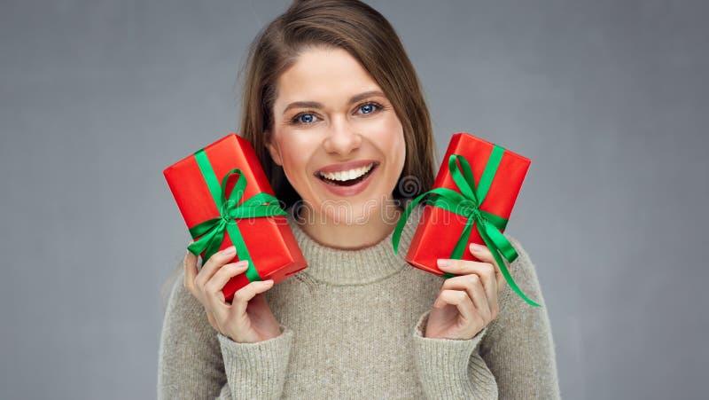 Jovem mulher feliz que guarda a caixa de presente de dois vermelhos foto de stock