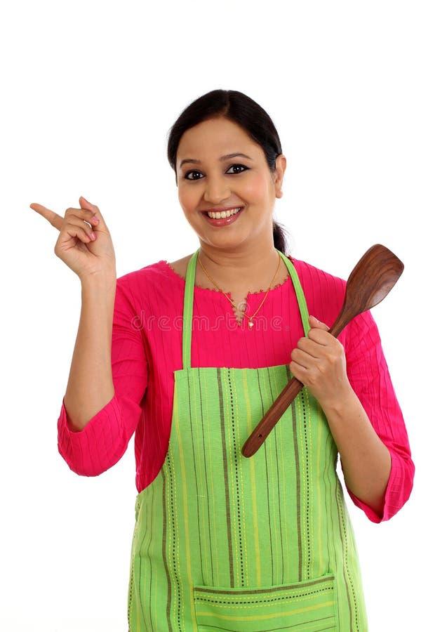 Jovem mulher feliz que guarda o utensílio da cozinha imagens de stock royalty free