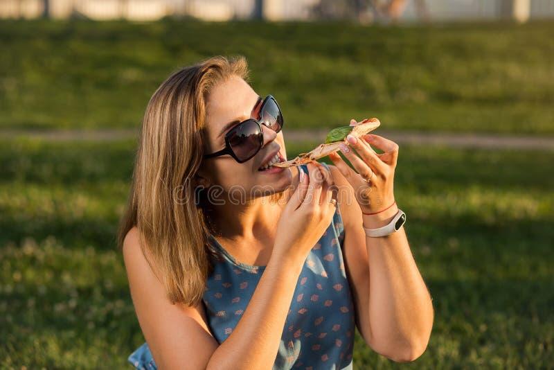 A jovem mulher feliz que guarda a pizza quente na caixa, assenta exterior no parque fotografia de stock