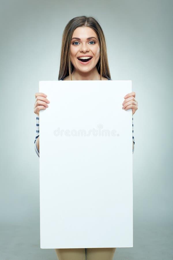 Jovem mulher feliz que guarda a placa branca do sinal fotos de stock royalty free