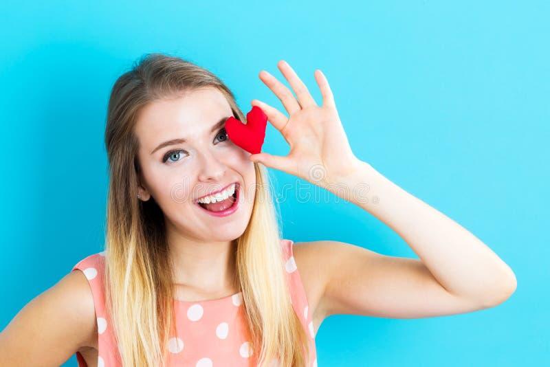 Jovem mulher feliz que guarda um coxim do coração fotos de stock royalty free