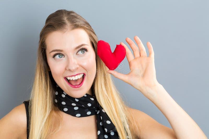 Jovem mulher feliz que guarda um coxim do coração imagem de stock royalty free