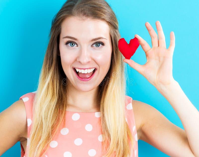 Jovem mulher feliz que guarda um coxim do coração imagem de stock