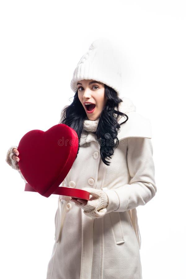 Jovem mulher feliz que guarda uma caixa de presente grande do coração fotos de stock