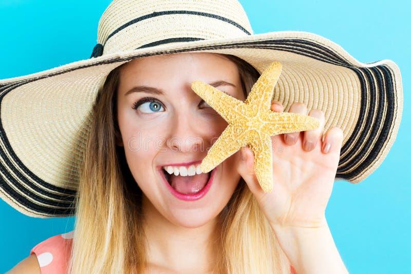 Jovem mulher feliz que guarda uma estrela do mar imagem de stock