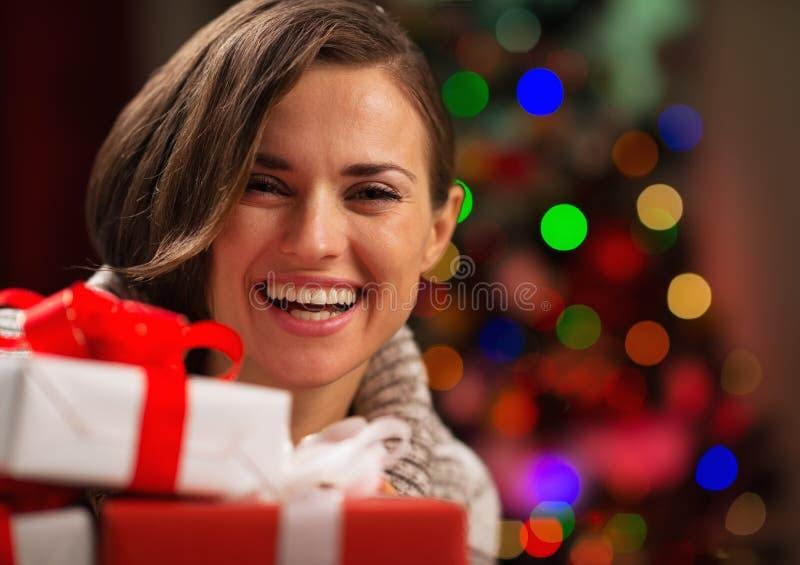 Jovem mulher feliz que guardara caixas de presente do Natal foto de stock