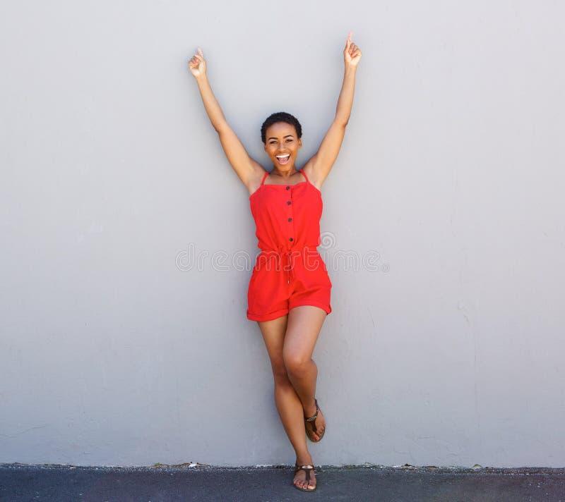 Jovem mulher feliz que inclina-se contra a parede cinzenta com os braços aumentados fotografia de stock royalty free