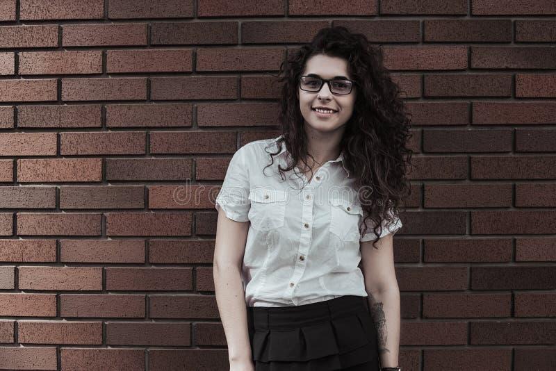 Jovem mulher feliz que levanta na câmera no fundo da parede de tijolo vermelho imagens de stock