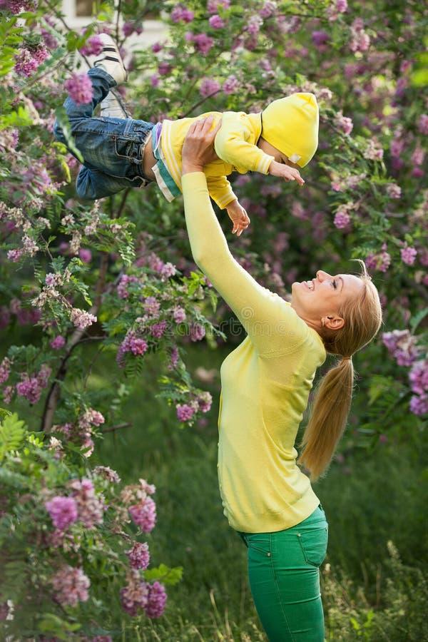Jovem mulher feliz que levanta sua elevação do filho acima imagens de stock