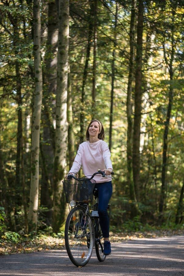 Jovem mulher feliz que monta uma bicicleta imagens de stock royalty free