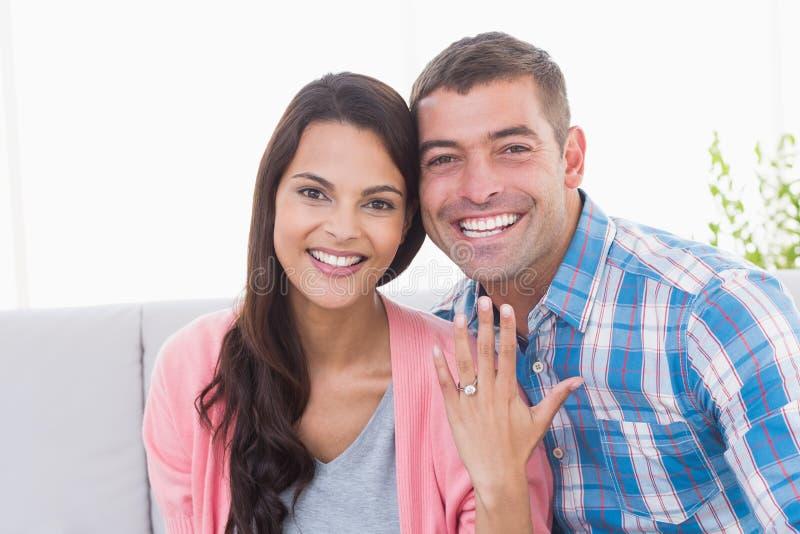 Jovem mulher feliz que mostra o anel ao sentar-se com homem fotos de stock royalty free