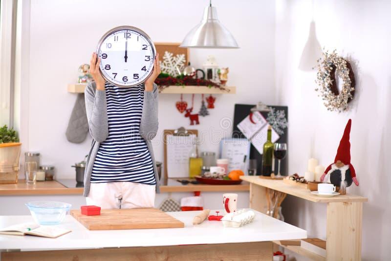 A jovem mulher feliz que mostra o pulso de disparo no Natal decorou a cozinha foto de stock