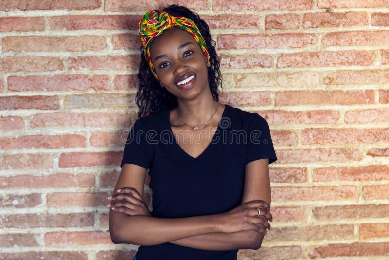 Jovem mulher feliz que olha a câmera com os braços cruzados ao estar na frente de uma parede fotos de stock