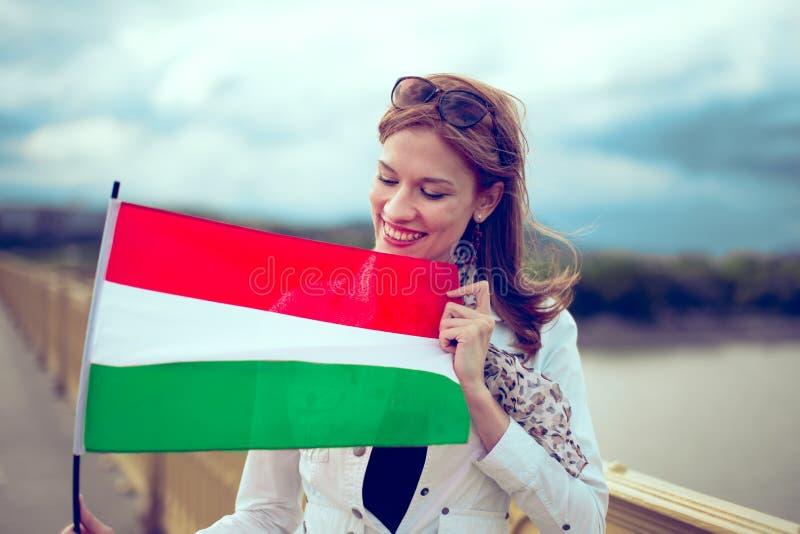 Jovem mulher feliz que olha e que guarda a bandeira húngara foto de stock royalty free