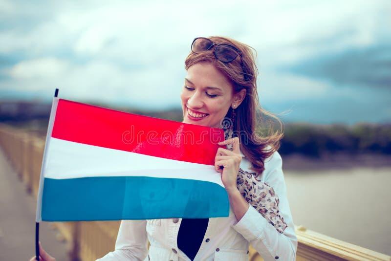 Jovem mulher feliz que olha e que guarda a bandeira holandesa foto de stock royalty free