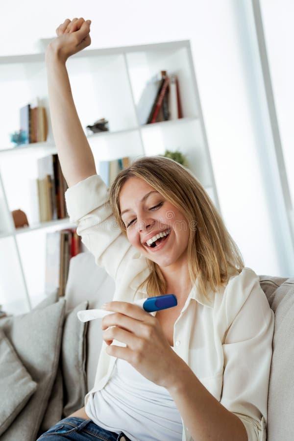 Jovem mulher feliz que olha o teste de gravidez com resultado positivo fotos de stock