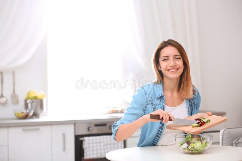 Jovem mulher feliz que prepara a salada na cozinha, espaço para o texto fotografia de stock royalty free