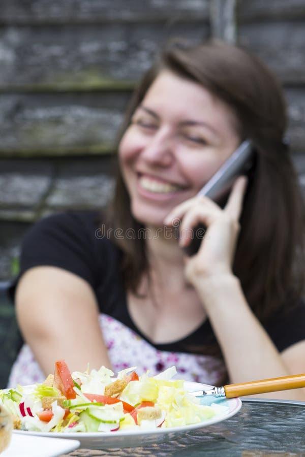 Jovem mulher feliz que recebe uma chamada imagem de stock
