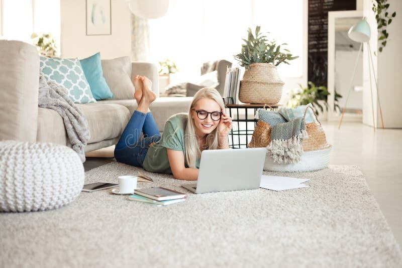 Jovem mulher feliz que relaxa em casa e que usa o portátil foto de stock royalty free