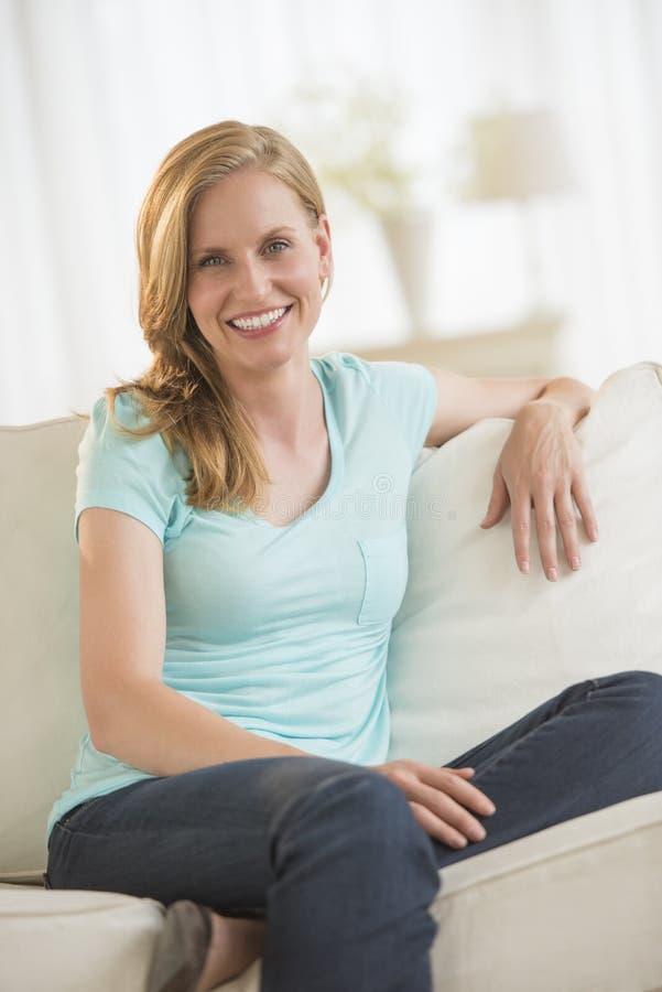 Jovem mulher feliz que relaxa no sofá fotos de stock